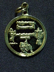 The back side of the WISH FULFILLING AND BUDDHA MANTRA BLESSING PENDANT has the images of the Victory Banner, Lung-Ta or Windhorse, the seed syllable of the Goddess Tara - TAM, and the symbolic script of the MEDICINE BUDDHA MANTRA, WISH FULFILLING MANTRA, and the NEGATIVE KARMA CLEANSING MANTRA.